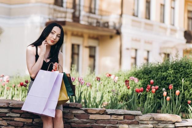 Modisch gekleidete frau mit farbigen einkaufstüten sitzen in der nähe von blumen auf der straße, shopping-konzept