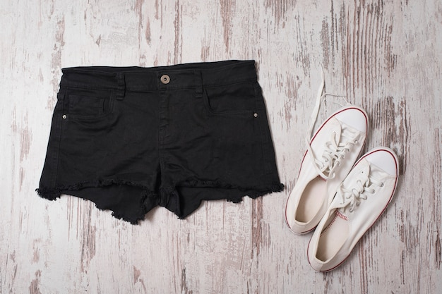 Modisch. schwarze shorts und weiße turnschuhe. ansicht von oben