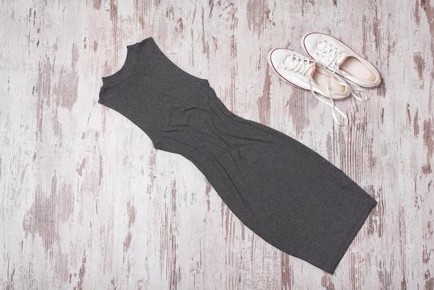 Modisch. weibliche sommergarderobe. graues kleid und weiße schuhe. ansicht von oben