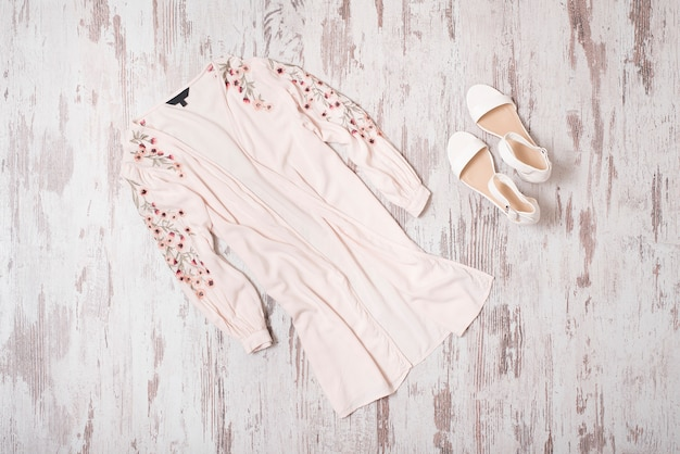 Modisch. weibliche sommergarderobe. rosa bestickte strickjacke und weiße schuhe. ansicht von oben