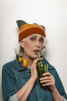Modische ältere frau in einer jeansjacke, die auf weißem hintergrund trinkt