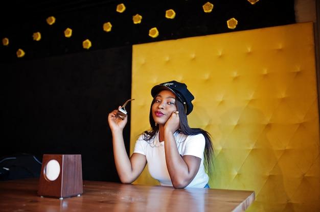 Modische afroamerikanerfrau in der schwarzen kappe, die im gemütlichen café kühlt.