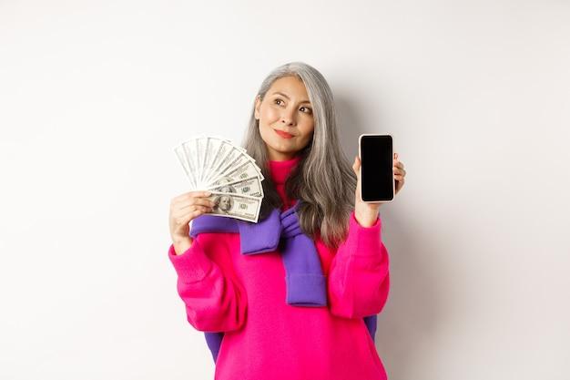 Modische asiatische seniorin, die gelddollar und leeren smartphone-bildschirm zeigt, online-shop demonstrieren, auf weißem hintergrund stehend