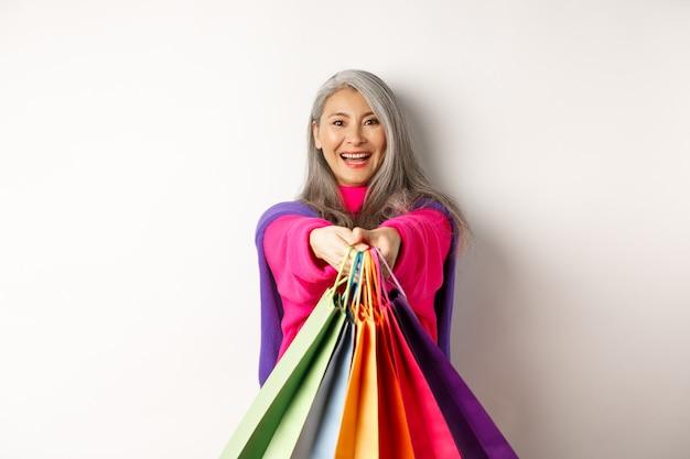 Modische asiatische seniorin, die weiter einkaufen geht, die hände mit papiertüten ausstreckt, zufrieden in die kamera lächelt und auf weißem hintergrund steht.