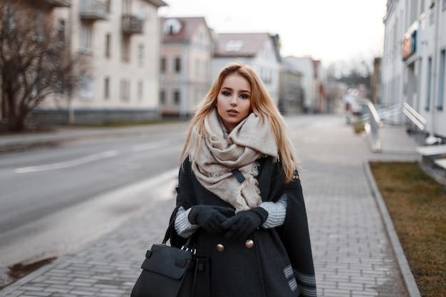 Modische attraktive junge blonde frau in einem vintage-strickpullover in einem stilvollen mantel in warmen handschuhen mit einem vintage-schal mit einer modischen schwarzen ledertasche, die auf der straße geht. stadt süßes mädchen.