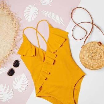 Modische bambustasche und sonnenbrille, strohhut und badeanzug. flache lage, ansicht von oben. sommerferien-konzept.