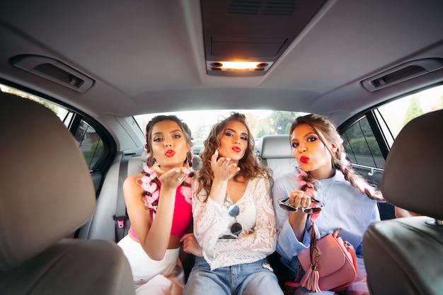 Modische beste freundinnen, die in das auto gehen und spaß haben, wenn sie zusammen sind