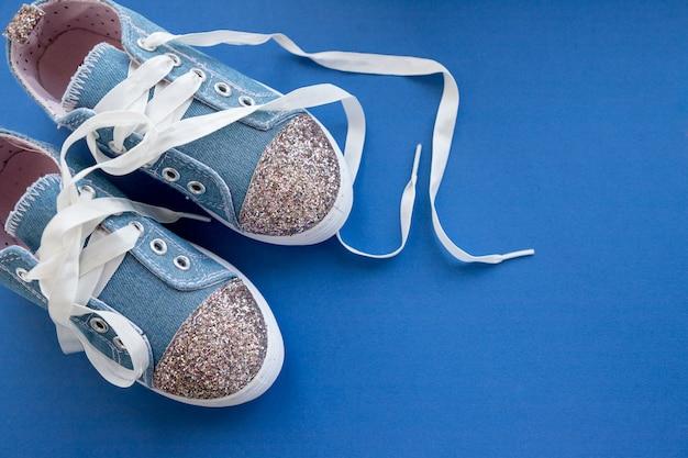 Modische blaue turnschuhe für mädchen lokalisiert auf blauer wand. paar trendige kindersportschuhe. randy denim sneakers für kinder. paar trendige glänzende sneakers mit weißen schnürsenkeln. jugendstil