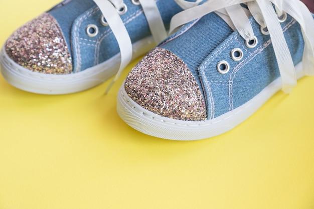 Modische blaue turnschuhe für mädchen lokalisiert auf gelber wand. paar trendige kindersportschuhe. randy denim sneakers für kinder. paar trendige glänzende sneakers mit weißen schnürsenkeln. jugendstil