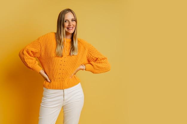 Modische blonde frau im orange stilvollen herbstpullover, der auf gelb aufwirft.
