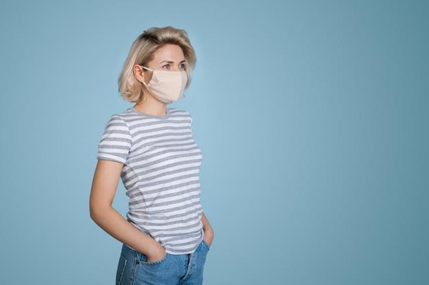 Modische blonde frau mit medizinischer maske auf gesicht, das auf blauer wand mit freiem raum aufwirft