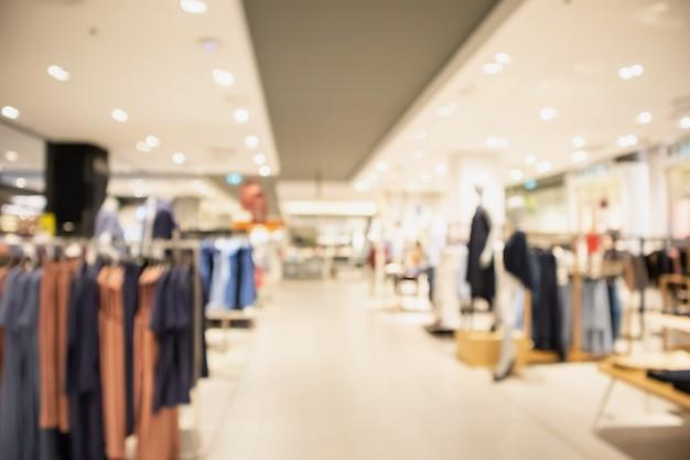 Modische boutique-bekleidungsgeschäftsfensteranzeige der frau im einkaufszentrum verwischen unscharfen hintergrund