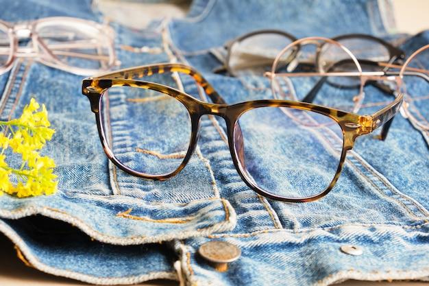 Modische brille an einer jeansjacke, eine alte jacke aus blue jeans und mehraugenbrille, trendige brillenfassungen