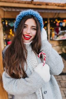 Modische brünette frau in den weißen handschuhen, die winterzeit genießen. außenporträt des raffinierten langhaarigen weiblichen modells im stilvollen blauen hut, der mit vergnügen am kalten morgen aufwirft, der weihnachtssüßigkeit hält.
