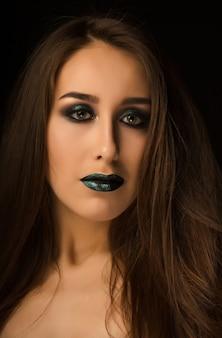 Modische brünette frau mit perfekter haut und kreativem metallisch-grünem make-up. nahaufnahmeportrait im studio auf dunklem hintergrund