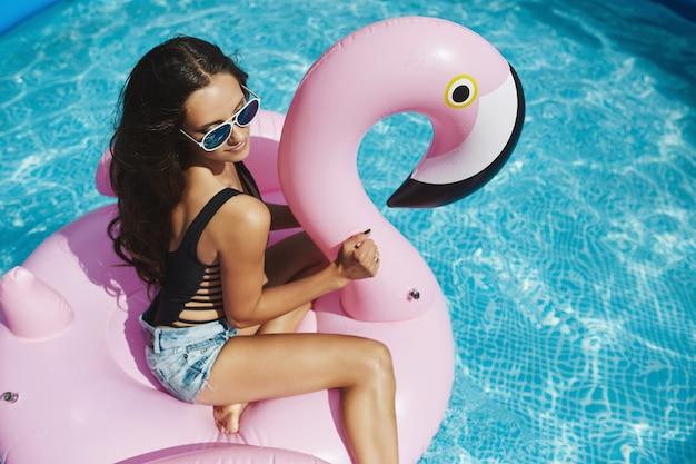 Modische brünette modelfrau mit sexy perfektem körper im stilvollen schwarzen bikini und in der glamourösen sonnenbrille, die auf einem aufblasbaren rosa flamingo am swimmingpool im freien aufwirft