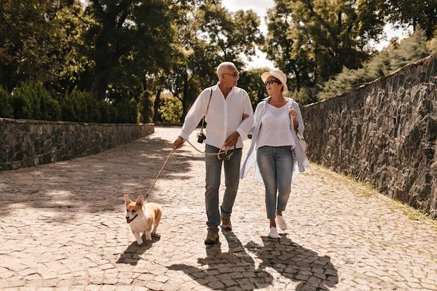 Modische dame mit kurzen haaren in gestreiftem hemd, jeans und hut, die mit grauhaarigem mann in heller kleidung mit hund im park gehen.