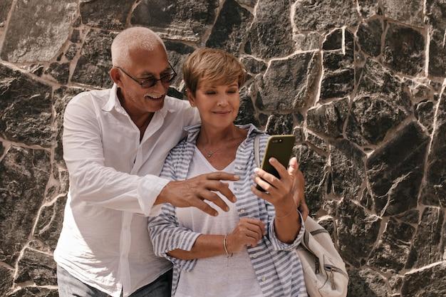 Modische dame mit kurzer frisur im weißen t-shirt und gestreifter bluse mit rucksack, der telefon mit altem mann im hemd betrachtet