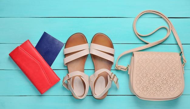 Modische damensandalen, ein reisepass, eine rote handtasche, eine ledertasche auf blauem holzboden. das konzept des reisens. draufsicht.