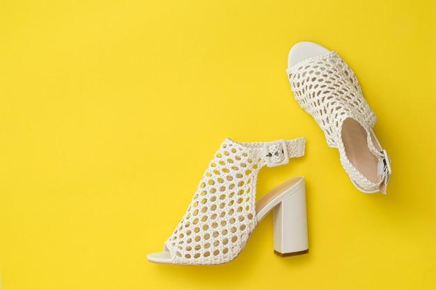 Modische damenschuhe aus geflochtenem weißem leder auf gelbem grund. sommerschuhe für frauen. flach liegen. der blick von oben.