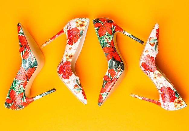 Modische damenschuhe. farbige damenschuhe auf gelbem, orangefarbenem hintergrund. bunte lederschuhe stiletto. stilvoller klassischer damen lederschuh. stilvolle damenschuhe in farben.