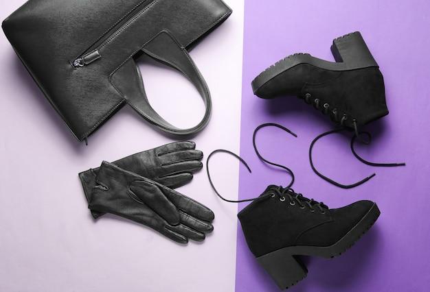 Modische damenschuhe und accessoires auf papierhintergrund. schwarze stiefel, lederhandschuhe, tasche. draufsicht. flach liegen