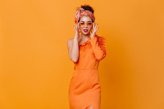 Modische dunkelhaarige dame im stirnband im afrikanischen stil, sonnenbrille und elegantes kleid blickt kokett in die kamera auf orangefarbenem raum.