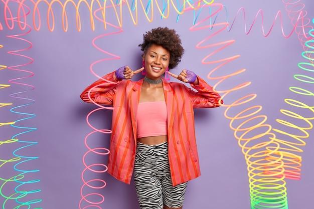 Modische dunkelhäutige frau zeigt auf ihre neuen ohrringe, kleider für disco, trägt stilvolle kleidung, lächelt breit, hat spaß