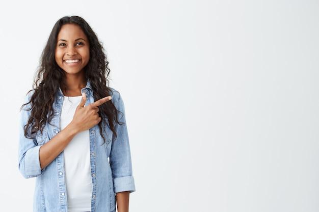 Modische emotionale junge afroamerikanische frau, die jeanshemd trägt, das ihren zeigefinger auf weiße leere wand hinter ihr zeigt, positiv und glücklich aussehend, breit lächelnd.