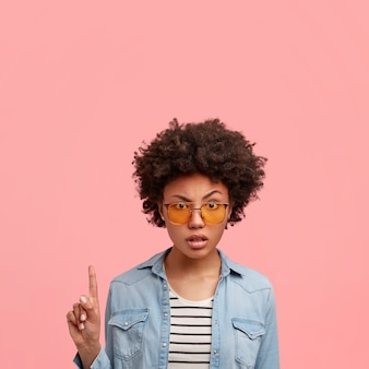 Modische, ernsthaft genervte, schöne afroamerikanerin in trendigen gelbtönen und jeansjacke, zeigt mit dem zeigefinger nach oben, zeigt oben freien raum, drückt negative emotionen aus.