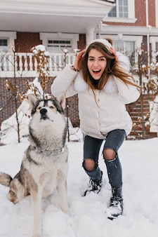 Modische erstaunliche frau, die spaß mit niedlichem husky hund draußen im schnee hat. glückliche winterzeit von echten freunden, haustieren, liebestieren