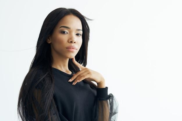 Modische frau afrikanisches aussehen schwarzes hemd langes haar posiert