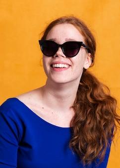 Modische frau des mittleren schusses mit sonnenbrille und breitem lächeln
