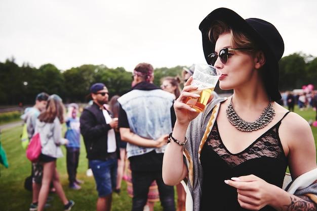 Modische frau, die beim festival ein bier trinkt