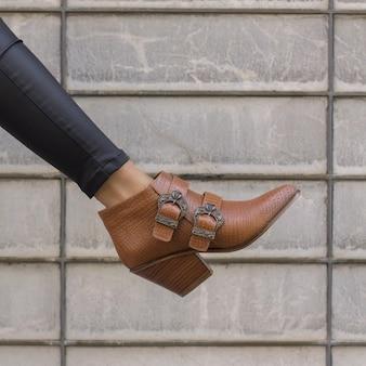 Modische frau, die einen braunen eleganten absatz mit krokodilmuster trägt, verziert mit gürteln