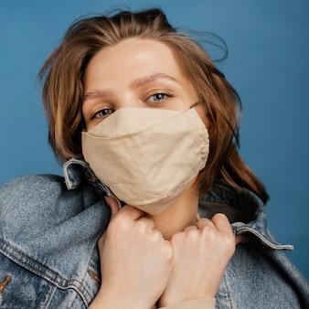 Modische frau, die jeansjacke und -maske trägt