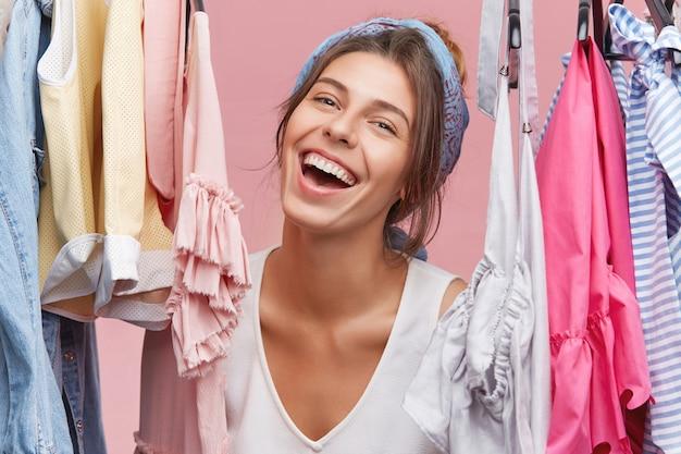 Modische frau, die kleid auf datum oder party wählt, sich aufgeregt und glücklich fühlt. fröhliche frau, die erfreut schaut, während sie tasche vor reise packt, in ihrem kleiderschrank mit gestellen voller kleidung stehend