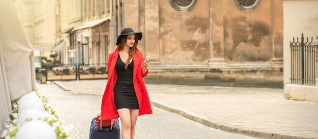 Modische frau, die mit reisekoffer geht