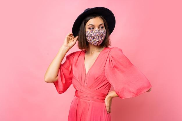 Modische frau gekleidet schützende stilvolle gesichtsmaske. trägt schwarzen hut und sonnenbrille. posieren über rosa wand