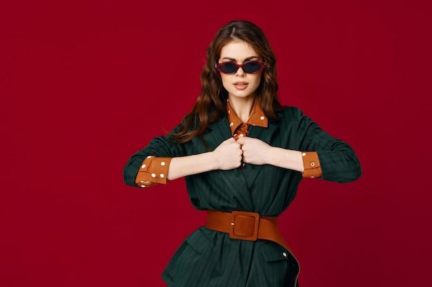 Modische frau im anzug gestikuliert mit den händen sonnenbrillen luxus rotem hintergrund