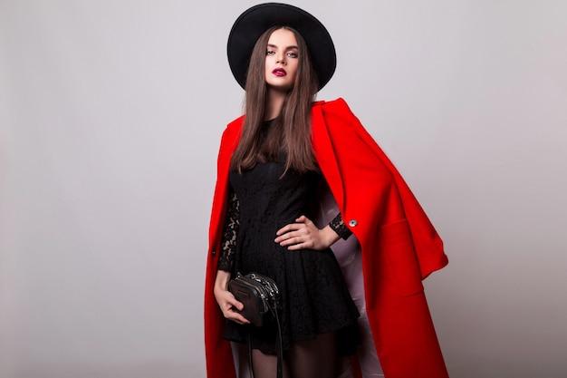 Modische frau im roten mantel und im schwarzen hut, der aufwirft