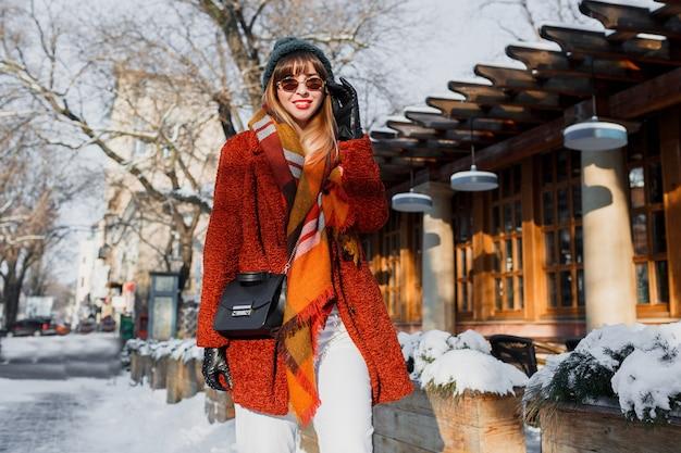 Modische frau im stilvollen winteroutfit, die durch die stadt geht