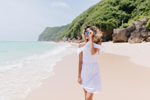 Modische frau im weißen outfit, die zeit auf tropischer insel verbringt. außenporträt der reizenden blonden frau, die naturansichten am resort genießt.