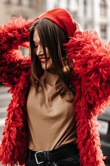 Modische frau in beigem oberteil und rotem mantel zieht baskenmütze im französischen stil an und geht durch die stadt.