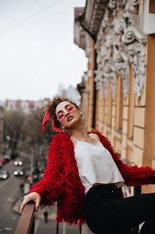 Modische frau in den roten brillen, die auf terrasse aufwerfen