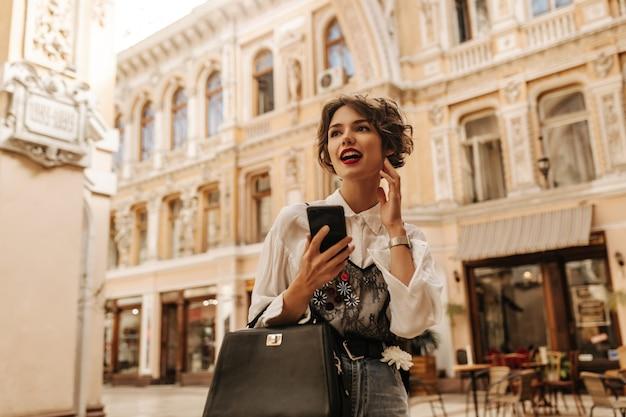 Modische frau in der hellen bluse mit spitze, die dunkle handtasche und telefon in der stadt hält. die wellige frau mit den hellen lippen schaut auf die straße.