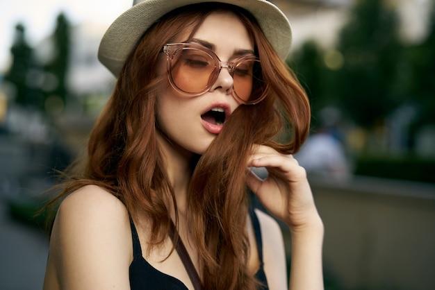 Modische frau in der straße mit schwarzem kleid, hut und brille