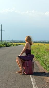 Modische frau in einem sommerkleid und stilettos, die von der kamera abgewandt sind, die am straßenrand auf dem land per anhalter fährt