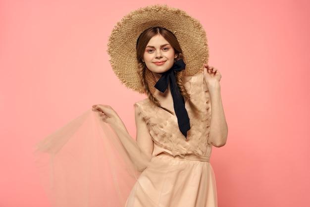 Modische frau in kleid und hut mit schwarzem band auf rosa