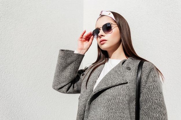Modische frau in stilvoller frühlingskleidung richtet an sonnigen tagen die sonnenbrille in der nähe der wand aus. süßes mädchen in trendigem outfit mit brille in bandana posiert an einem sonnigen tag auf der straße in der stadt. jugendstil.